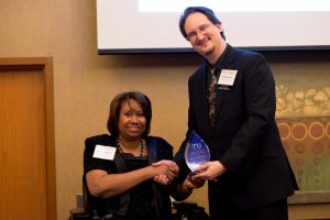 Transit Activist of the Year Awardee Lisa Franklin receiving the award from TRU chair Kelly Logan