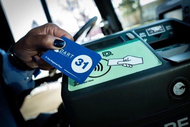 A hand of an African-American person with pretty black nailpolish holding a blue Dart card up to a card reader