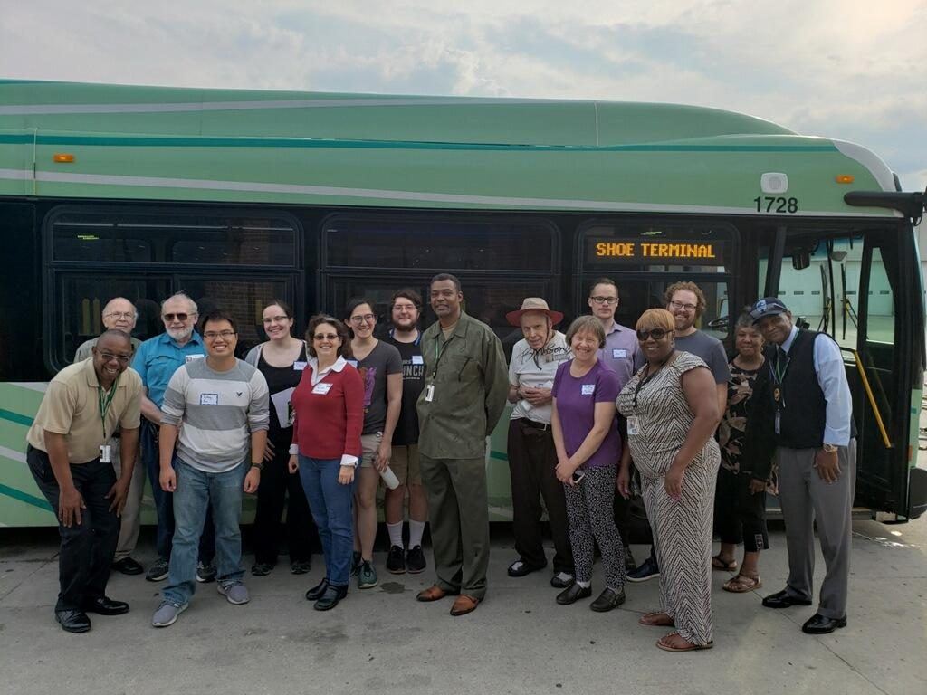 TRU staff, supporters, and DDOT staff pose in front of a new, green bus that says SHOE TERMINAL on its destination sign. Everyone is smiling.
